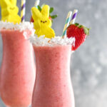 Bunny Colada in a glass with strawberries, coconut and peeps garnishing it with a straw