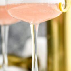 glass of cranberry gin fizz with lemon twist