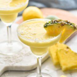 two sugared rim glasses of malibu pineapple margarita with coconut
