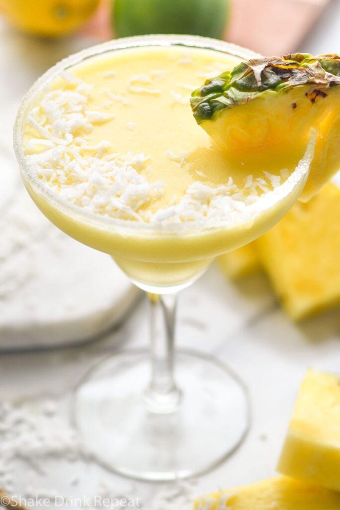 sugared rim glass of pineapple malibu margarita with pineapple garnish and coconut