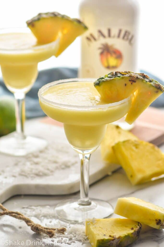 two sugar rimmed glasses of blended malibu pineapple margarita with pineapple garnish