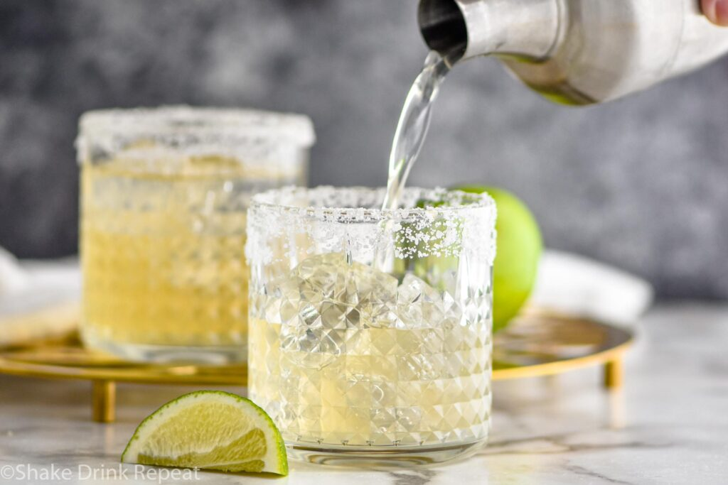 two glasses of margarita with salted rim, ice and lime