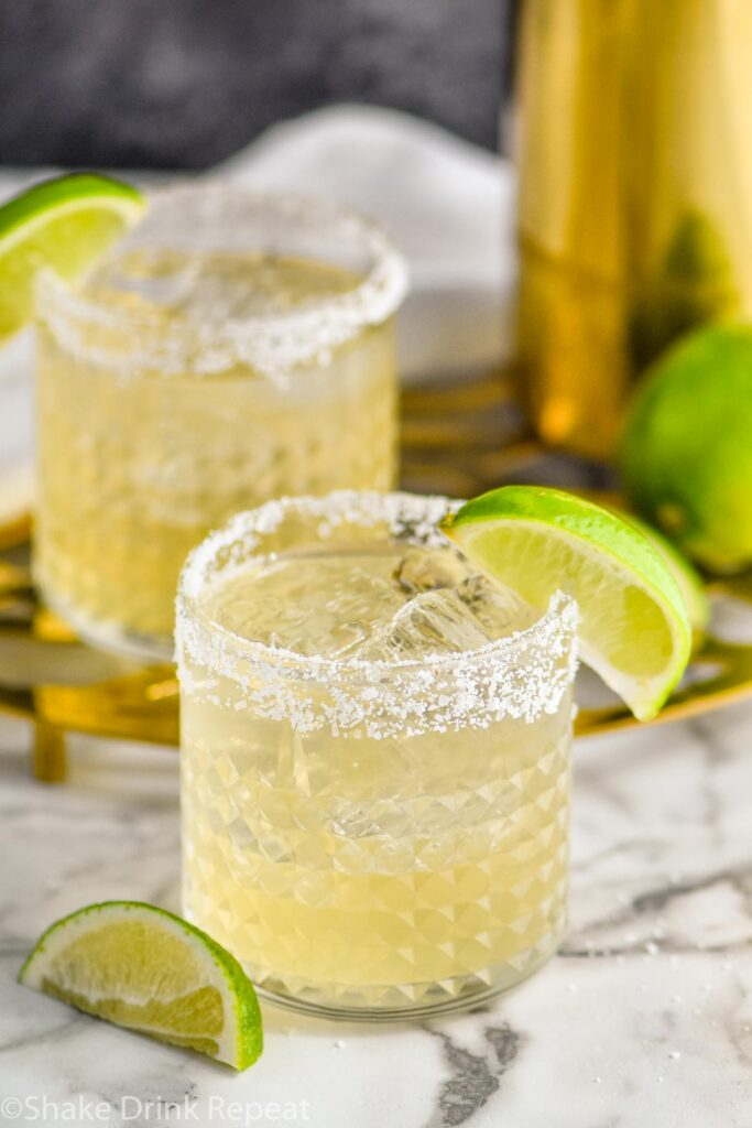 two glasses of margarita with salted rim, ice and limes