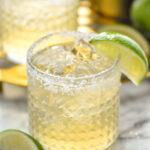 two glasses of margarita with ice, salted rim and lime