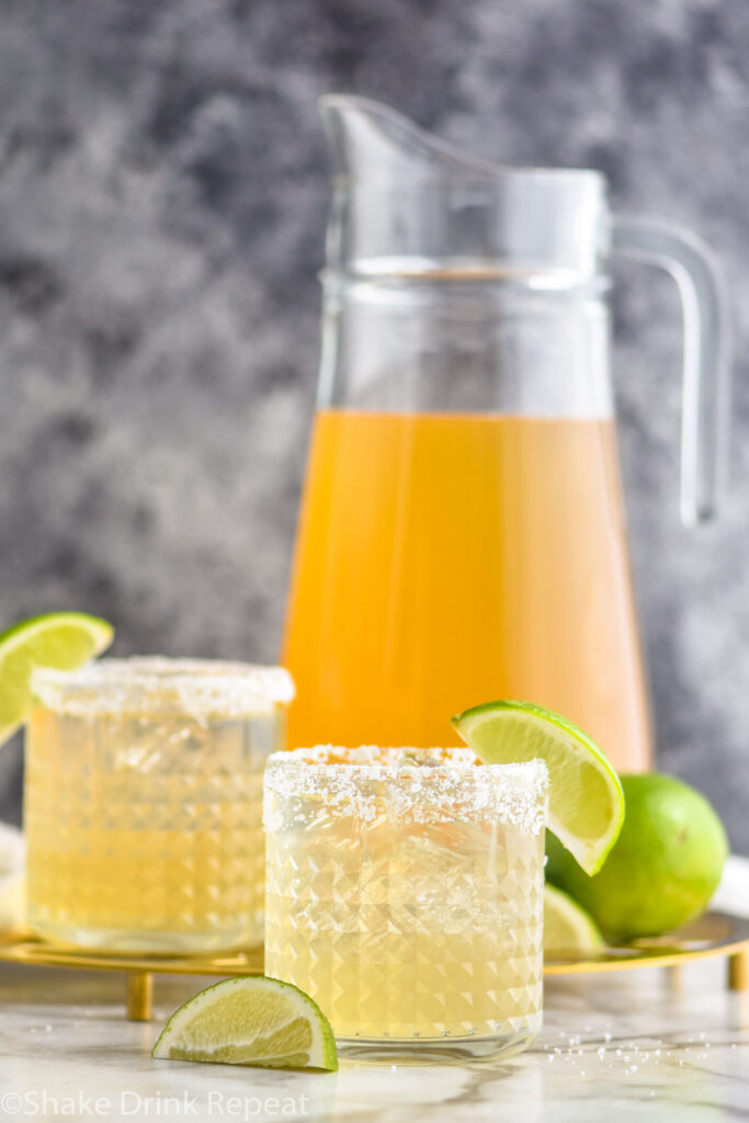 pitcher and two glasses of margarita with salted rim, ice, limes
