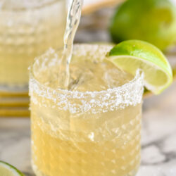 glass of margarita with ice, salted rim, and lime
