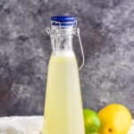 bottle of homemade margarita mix with lemons and limes