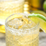 glass of homemade margarita with salted rim, ice, and lime