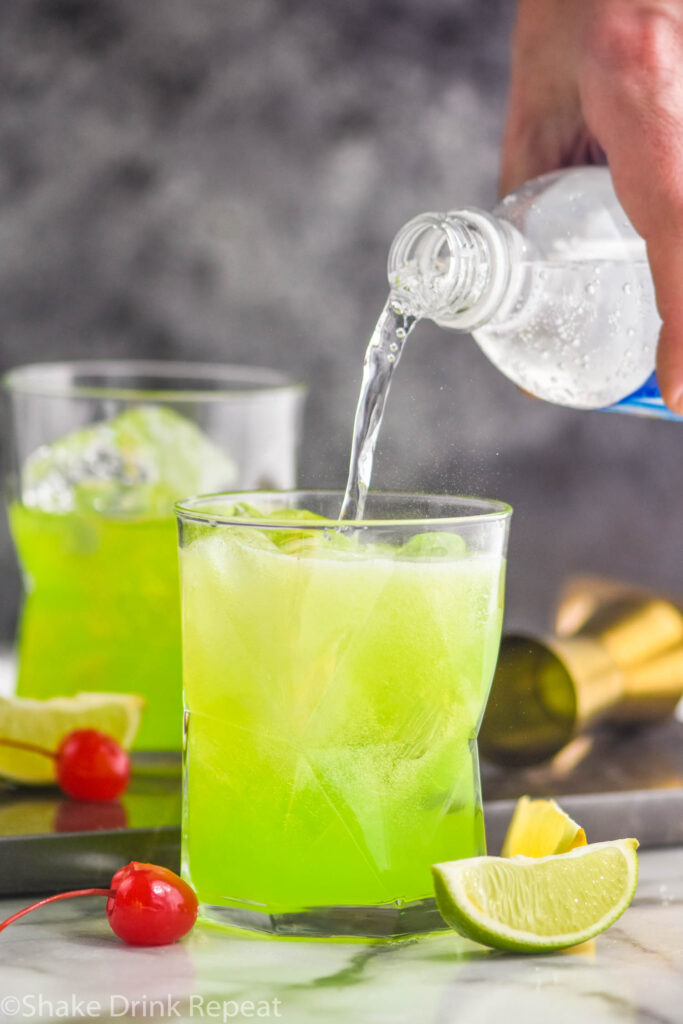 two glasses of midori sour wtih ice, lime, cherry, and club soda water