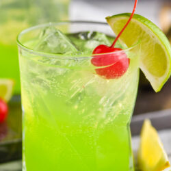glass of midori sour cocktail with ice, lime, and cherry