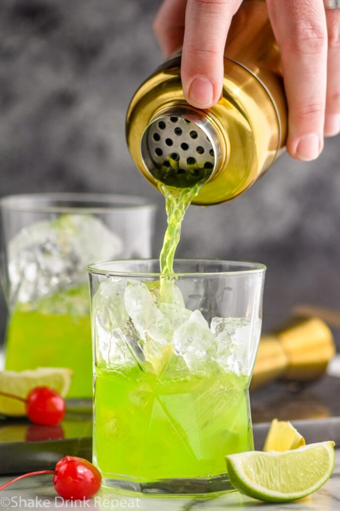making a midori sour in a shaker and pouring into a glass with ice, lime, and cherry
