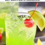 glass of midori sour with ice, lime, and cherry garnish