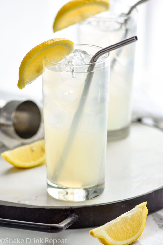 two glasses of rum collins with ice, lemon, and straws