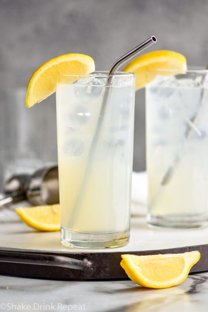 two glasses of rum collins with ice, lemons and straws.