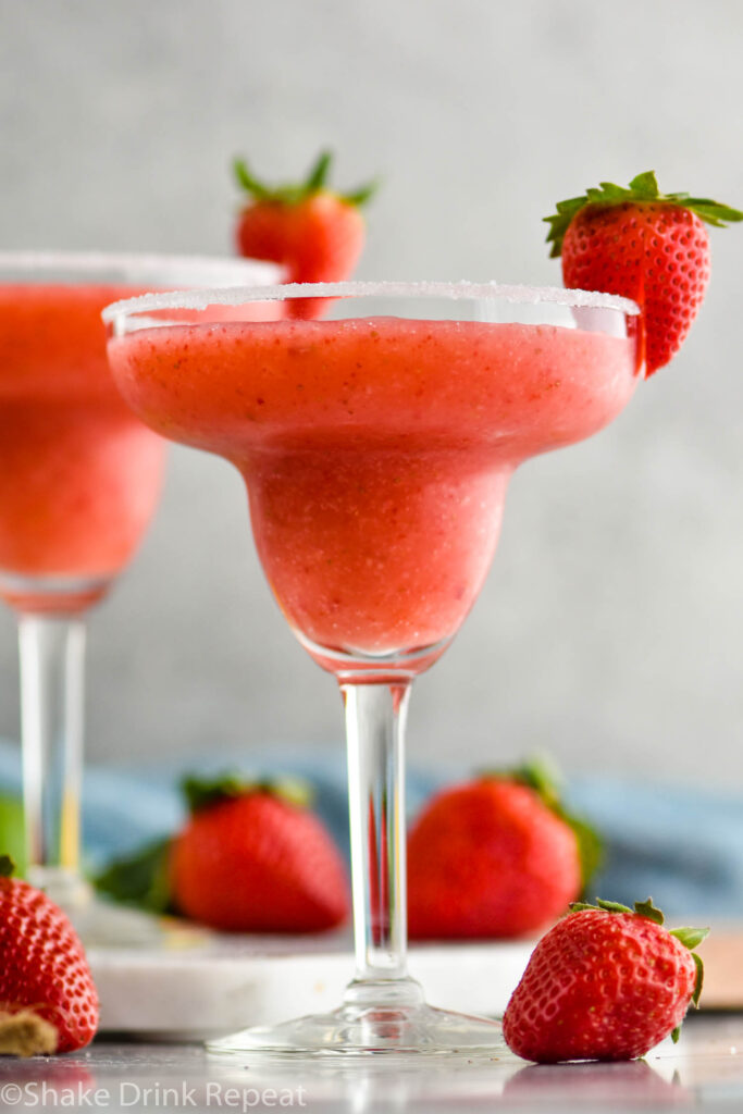 two glasses of frozen strawberry margarita with sugared rim and fresh strawberries