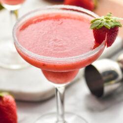 glass of frozen strawberry margarita with sugared rim and fresh strawberry garnish