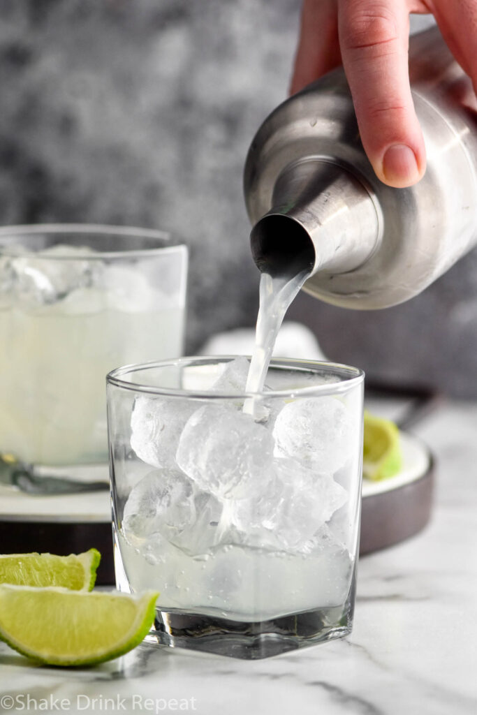 making a vodka gimlet recipe with a shaker in a glass with ice and limes