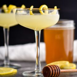 two glasses of bees knees cocktail with honey syrup and lemon twist garnish