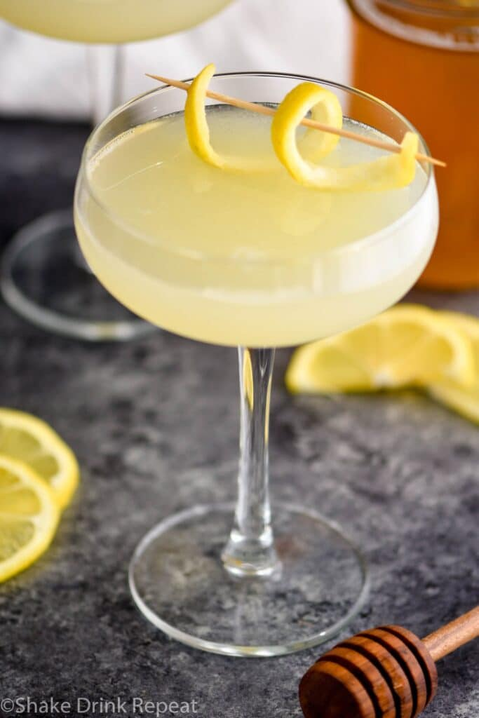 glass of bees knees cocktail with lemon and honey syrup