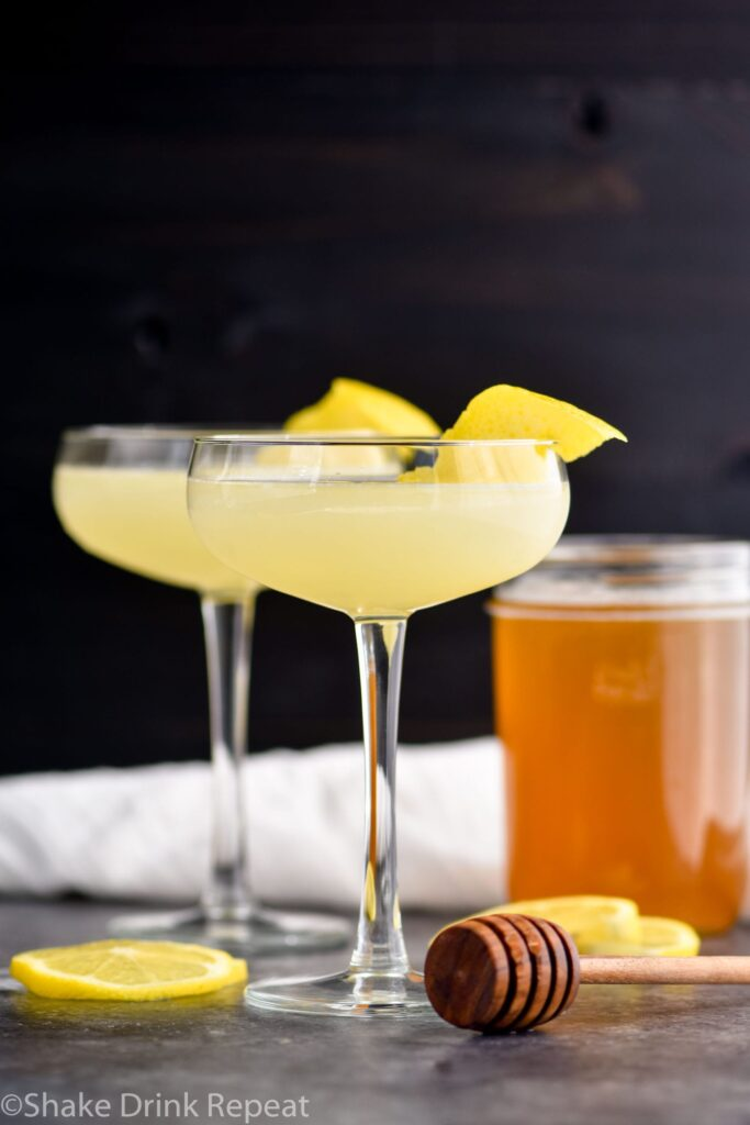 two glasses of bees knees cocktail with lemon and honey syrup