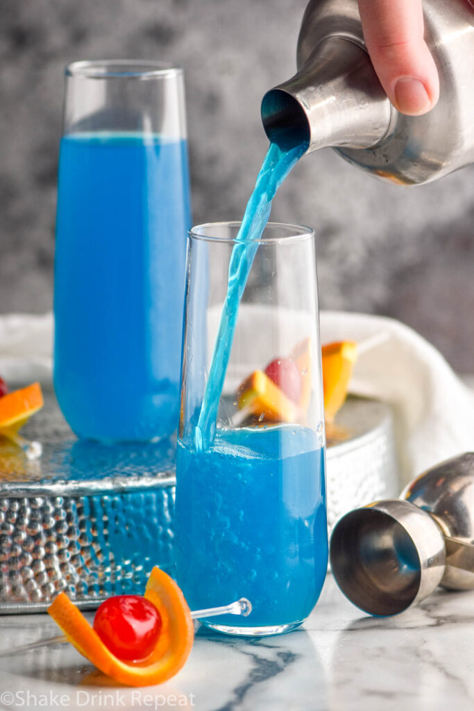 two glasses of blue kamikaze recipe with orange and cherry garnish