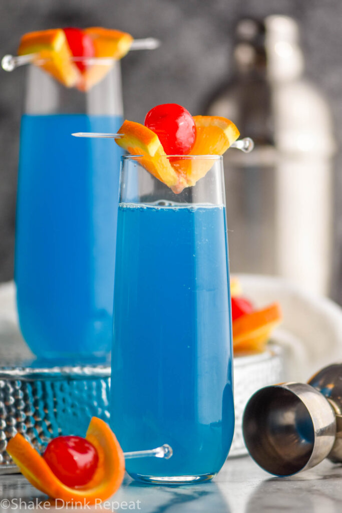two glasses of blue kamikaze cocktails with orange and cherry garnish