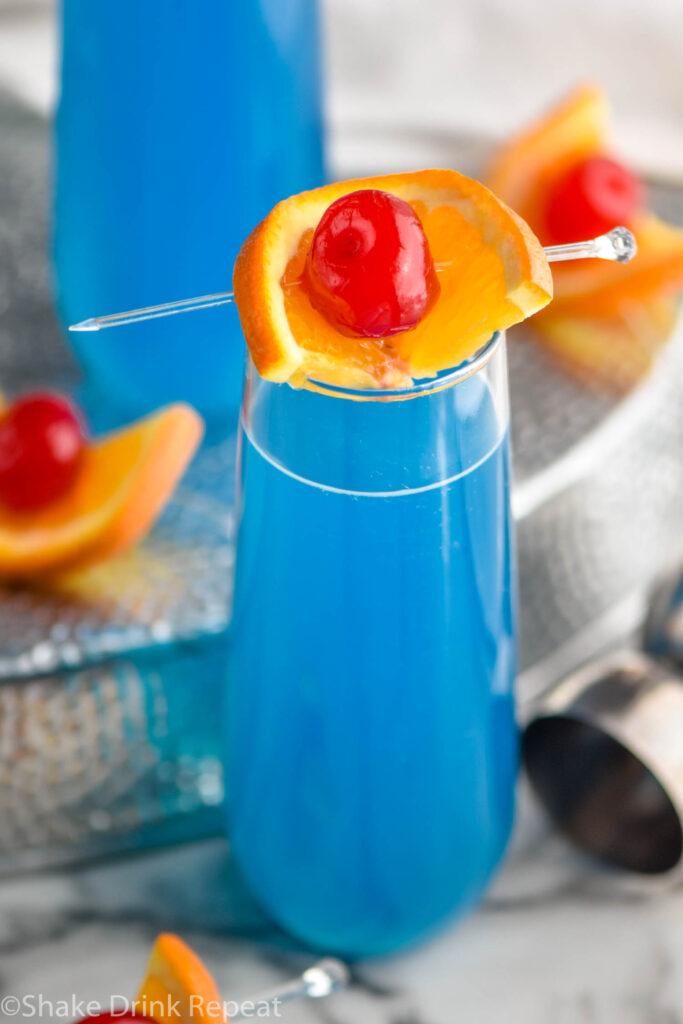 glass of blue kamikaze cocktail with orange and cherry garnish