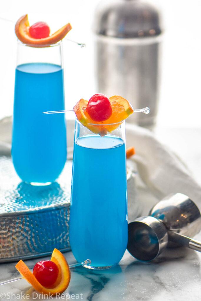 two glasses of blue kamikaze with orange and cherry garnish