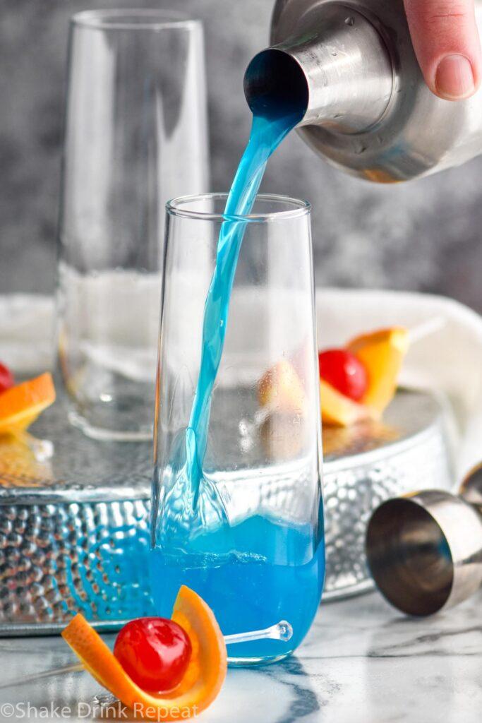 making glass of blue kamikaze with orange and cherry garnish