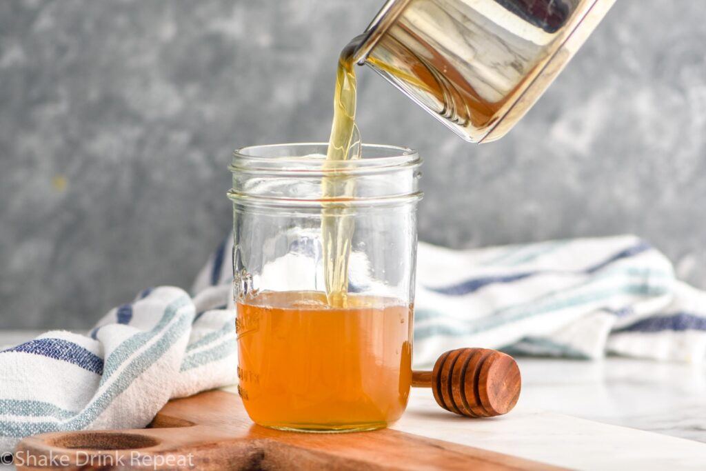 making homemade honey syrup recipe and pouring into jar