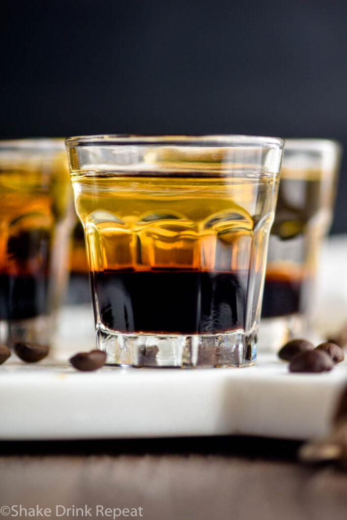 glass of layered mind eraser shot surrounded by coffee beans