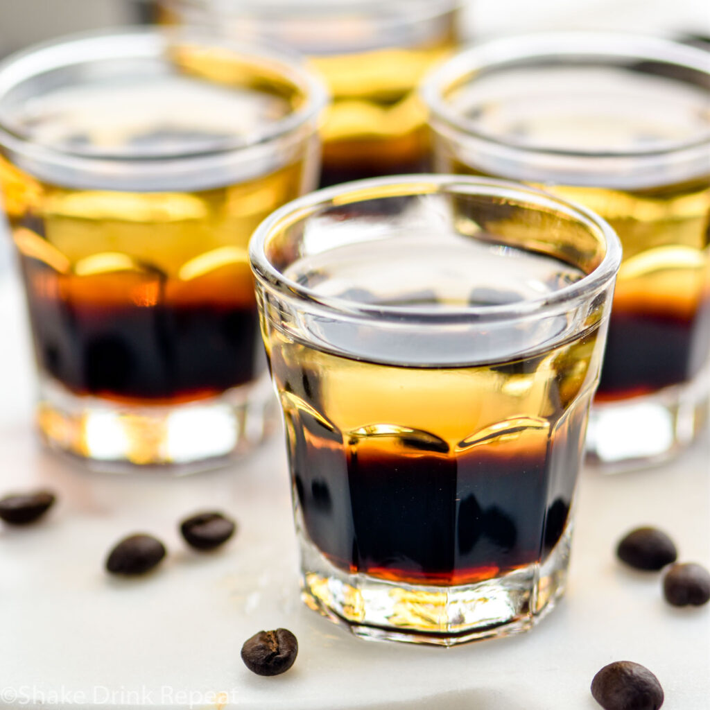 glasses of layered mind eraser shots surrounded by coffee beans
