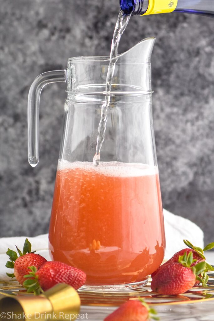 pitcher of strawberry margarita sangria with white wine poured in