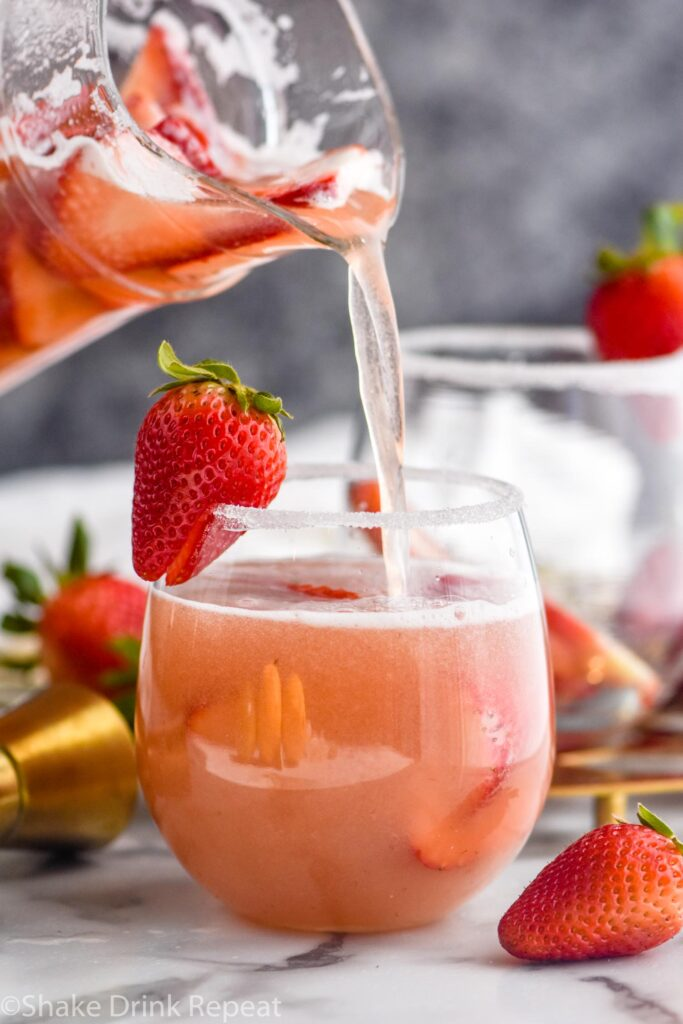 glass of strawberry margarita sangria with sugar coated rim and strawberry garnish