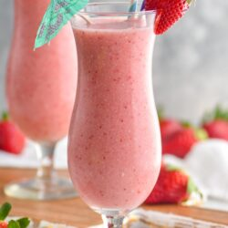 two glasses of strawberry colada drink with straws and umbrella