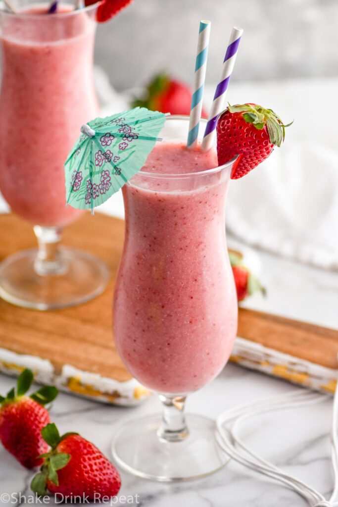 two glasses of strawberry colada cocktail with straws and umbrella