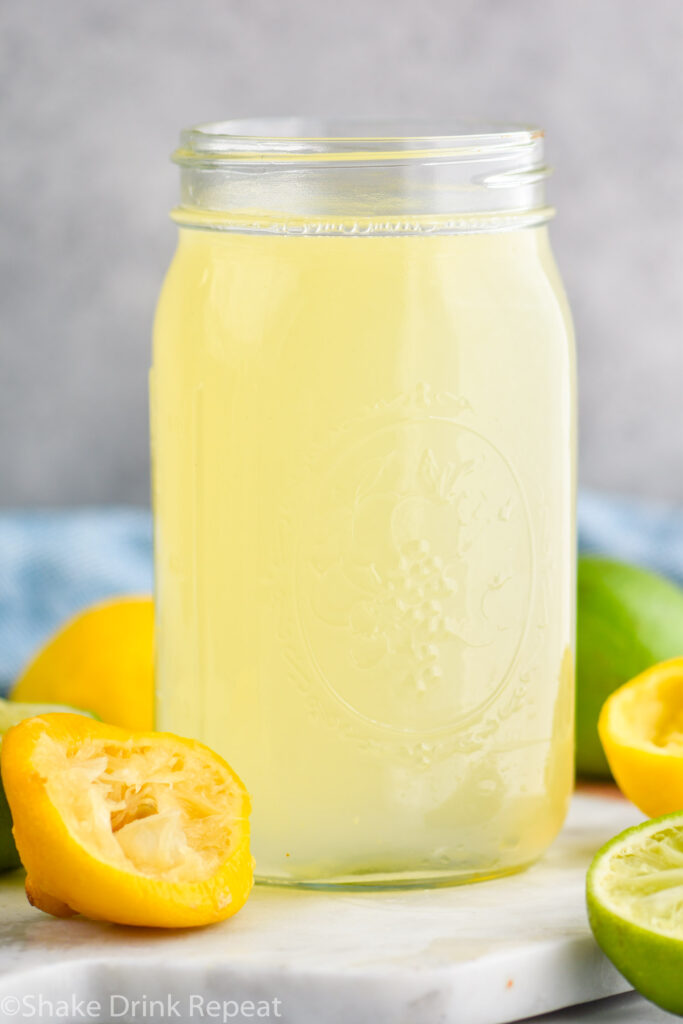 jar of homemade sweet and sour mix with lemons and limes