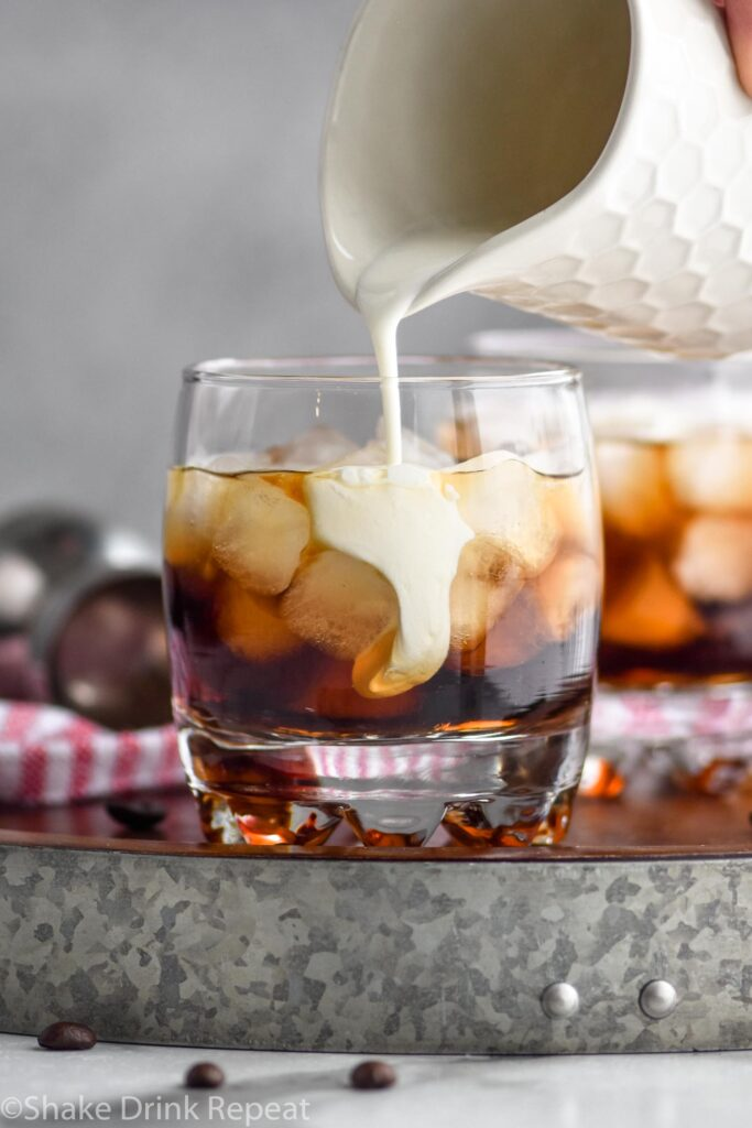Glass of white russian cocktail with ice and cream being poured surrounded by coffee beans