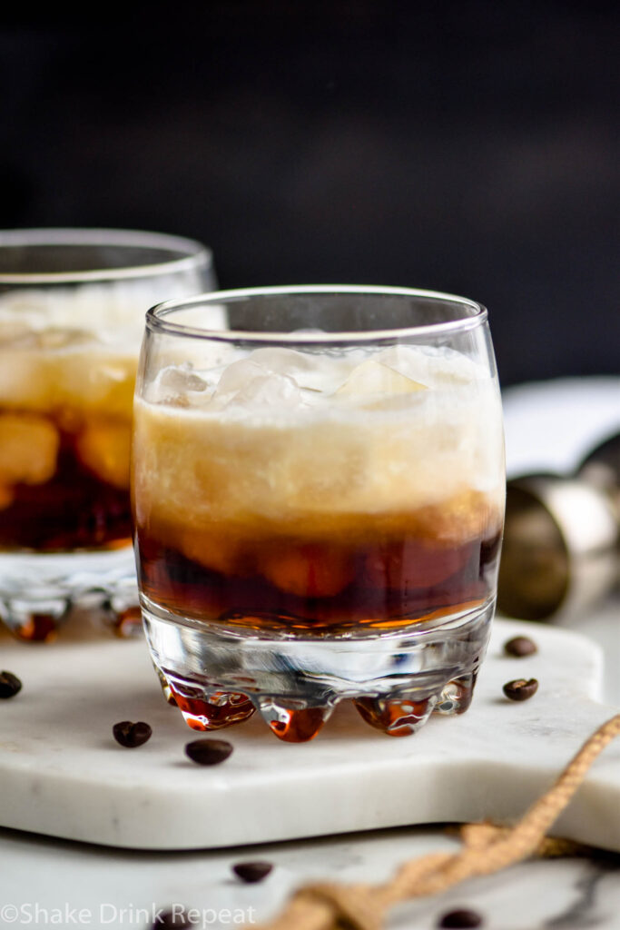 two glasses of white russian cocktail with ice and coffee beans