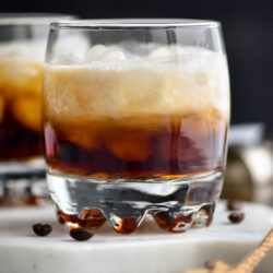 Glass of white russian cocktail with ice and coffee beans
