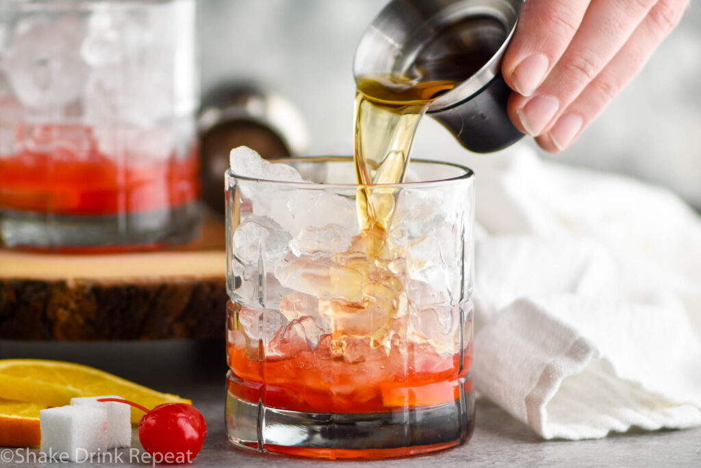 glass of wisconsin old fashioned ingredients with ice, sugar cube, brandy, cherry, and orange