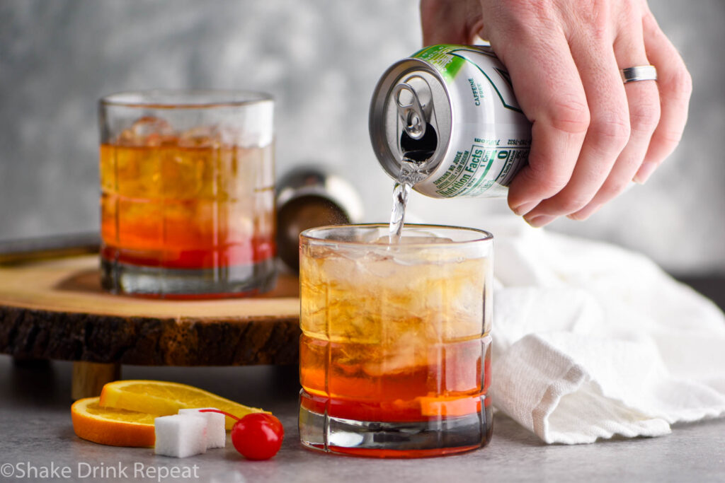 two glasses of wisconsin Old Fashioned with ice, sugar cube, cherry, orange, and lemon-lime soda