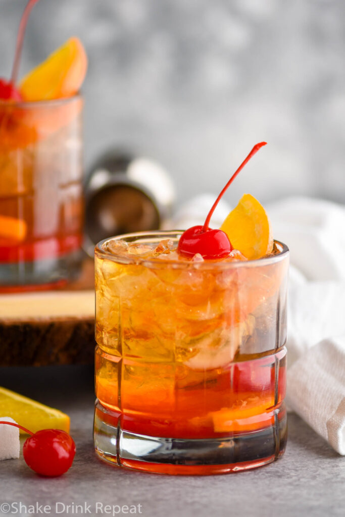glass of wisconsin old fashioned with ice, orange, and cherry