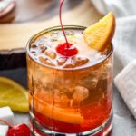 glass of wisconsin old fashioned with ice, cherry, and orange