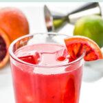 glass of blood orange margarita with ice and blood orange wedge garnish