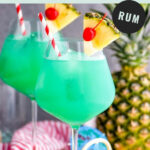 two glasses of blue hawaii with ice, straws, pineapple, and cherry