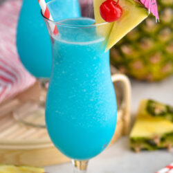 two glasses of frozen blue hawaiian with straw, umbrella, pineapple, and cherry