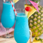 two glasses of frozen blue hawaiian with straw, umbrella, pineapple, and cherry garnish