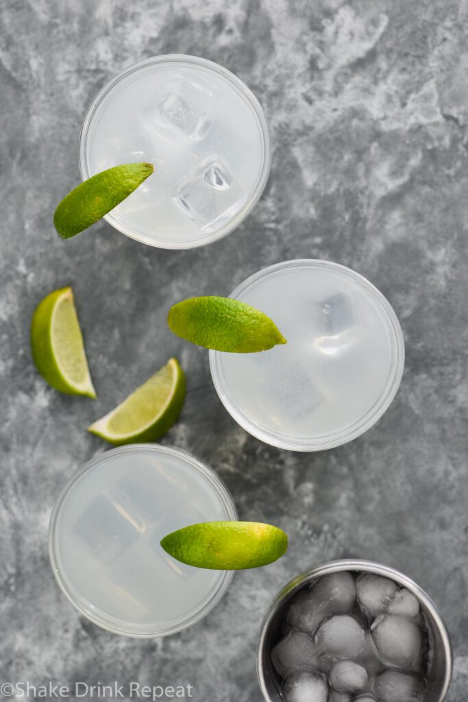 three glasses of gin gimlet with ice and lime wedges