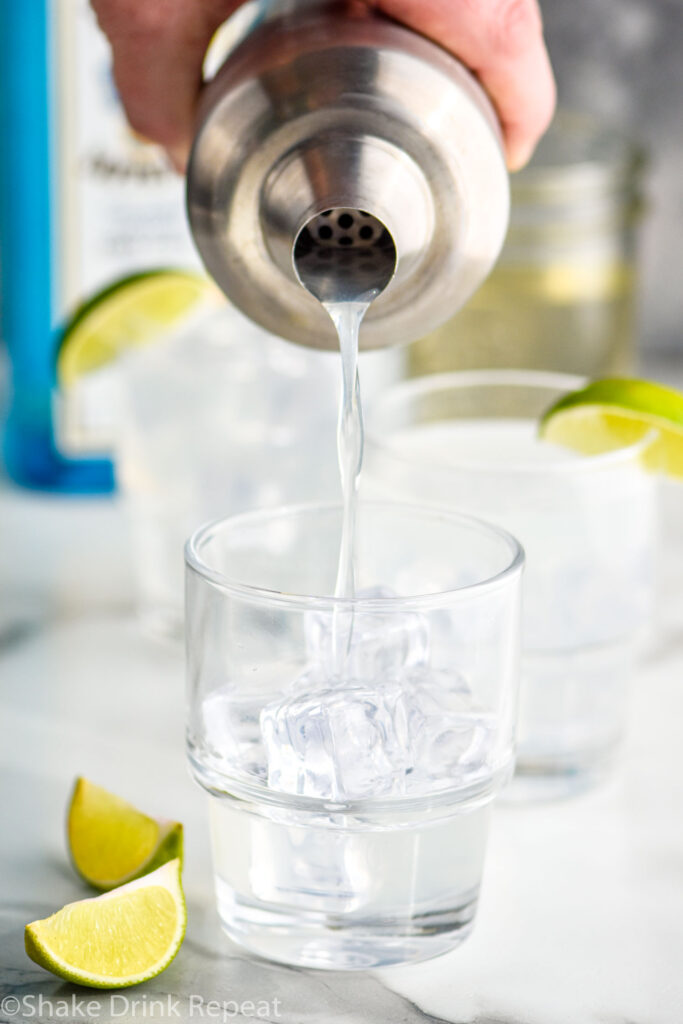 man pouring gin gimlet recipe from a shaker into a glass filled with ice and surrounded by lime wedges